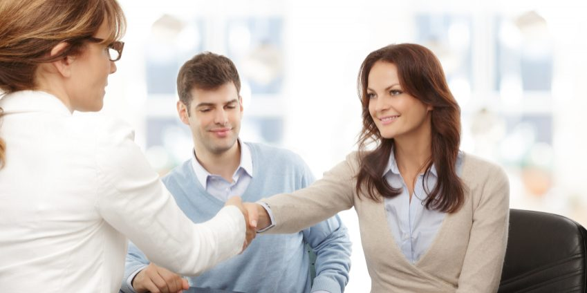 Contemporary young couple get financial advise and shaking hands.