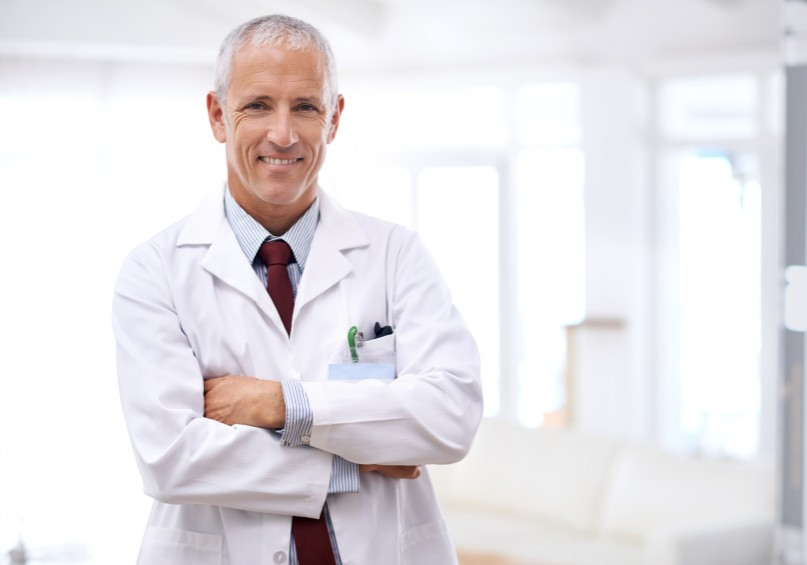 Portrait of a mature doctor standing with his arms folded